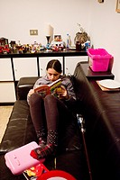 Llittle girl reading a book on the couch at home