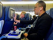 San Francisco, CA, USA, Chinese MAn Sitting on Airplane Watching onboard Film on Seat Screen