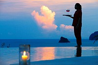 Six Senses Resort, Koh Yao Noi, Phang Nga Bay, Thailand, Asia. Waitress with a glass of wine in the restaurant near the swimming pool called The Hillt...