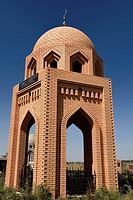 Yellow brick mausoleum with dome at Roadside Muslim cemetery near Shelek Kazakhstan.