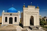 Hilal crescent moon symbols on Muslim brick mausoleums at a cemetery near Shelek Kazakhstan.