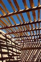 Diagonal shadows of ceiling beams and slats on mud brick walls of unfinished house near Shymkent Kazakhstan.
