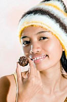 Young woman eating a chocolate