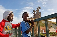 children in front of the African Renaissance Monument, 49 meter tall bronze statue located on top of one of the twin hills known as Collines des Mamel...