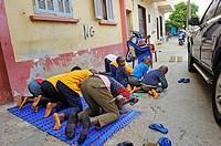 Muslim children praying in the street, Medina district, Dakar, Senegal, West Africa.