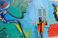 Senegalese graffiti artist Docta beside a collective mural in Medina district, Dakar, Senegal, West Africa.