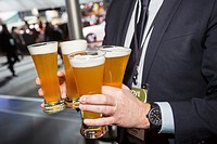 Detroit, Michigan - A man carries four glasses of beer while attending the North American International Auto Show.