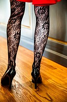Close up of woman´s legs wearing lace stockings, high heels and a red dress standing on wood flooring in a home.