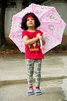 Little Indian girl enjoying rains with pink umbrella.