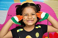 Little smiling Indian girl showing hands painted with Indian tri colour.