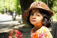 Close-up of little Indian girl wearing hat posing for camera.
