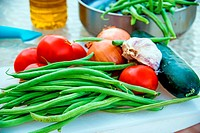 green beans ,tomatoes and garlic, raw on a desk.