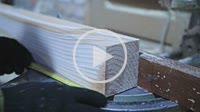Circular saw cutting wooden plank in workshop.