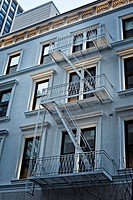 Looking Up at a Manhattan, New York City Rehabilitated Tenement Apartment Building. Late Day Light Reflecting on Windows and Fire Escape.