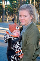 Young mother with baby in a forest in Ystad, Sweden.