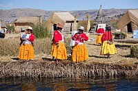 Aymara women in traditional dress waiting for welcoming the tourists, Uros Islands, Lake Titicaca, Puno Region, Peru, South America