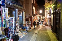 Tourists and souvenir shops selling Moroccan handicrafts at night, Granada, Andalusia, Spain, Europe.