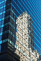 New York City. Apartment Building Reflected in the Facade of a Glass Paneled Office Building.